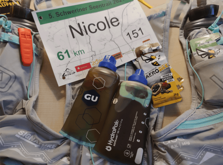 running vest, honey gels and race bib sitting on a table
