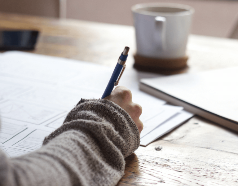 someone journaling on paper. Shown is the arm, paper journal and a cup sitting on a table