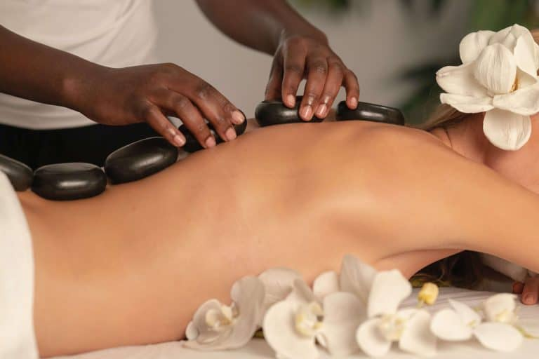 woman lying on her belly and getting a massage with stones
