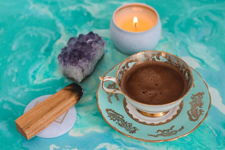 tea cup, candle and crystal sitting on a table